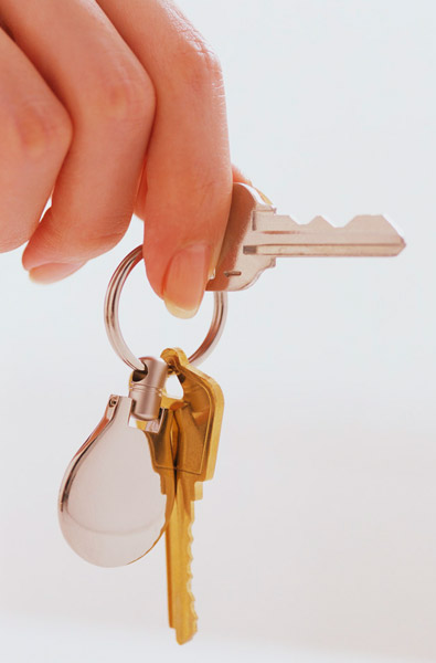 House key opening a front door of a new property